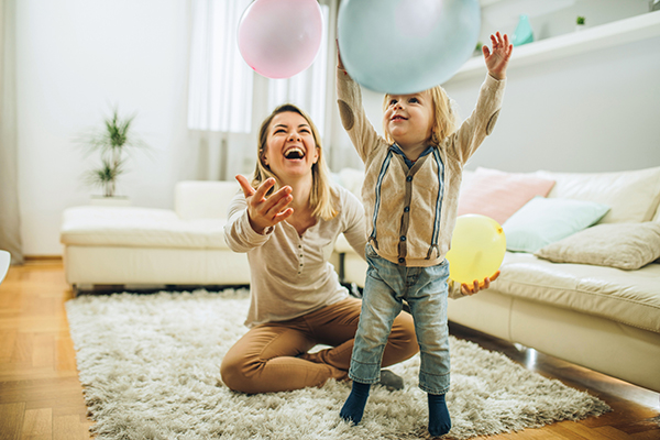 Happy mother and her small son playing with a balloons at home. Focus is on boy.