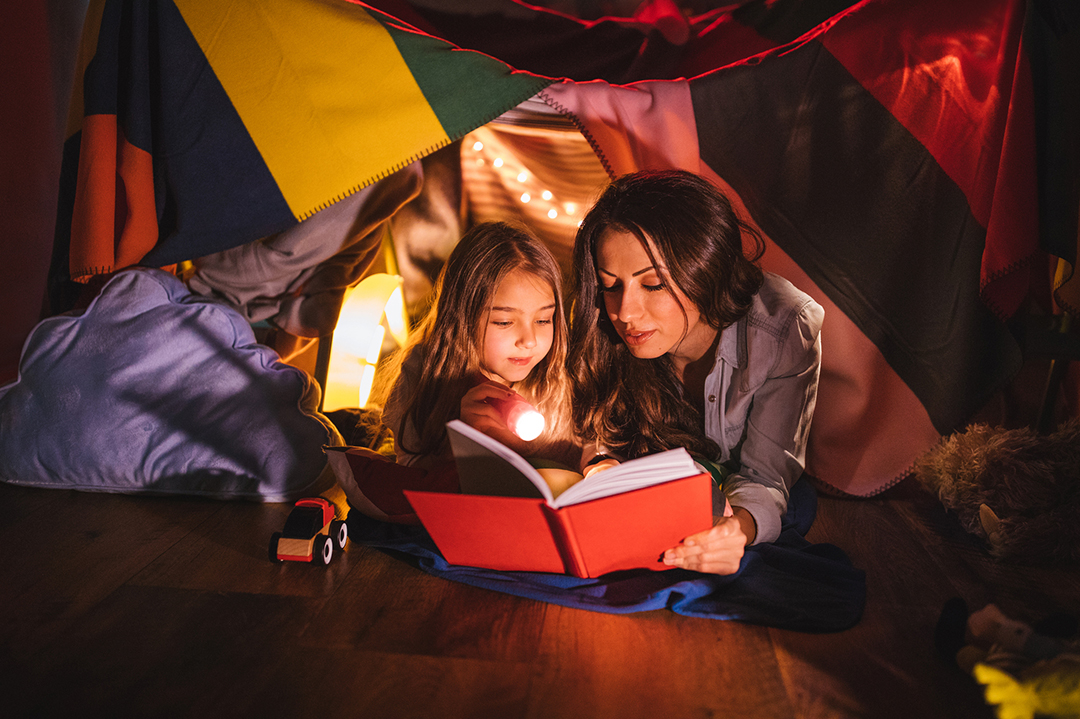 Mother reading a fairy tale book to her daughter under children's blanket fort at night