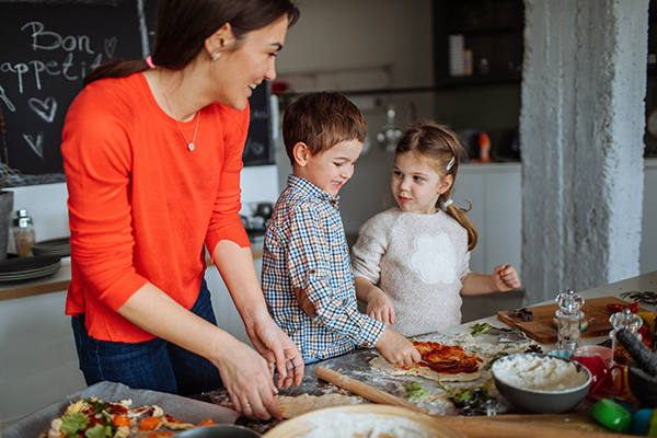 Photo of a cute little children preparing pizza in the kitchen, with a little help from their mom