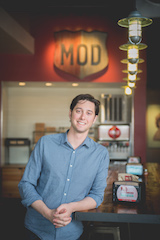 Jake Schostak<br>MOD Pizza Brand Leader, TEAM Schostak Family Restaurants<br>Livonia<br><b>Why the nominee is a SEEN Changemaker</b><br>As a fourth-generation leader at TEAM Schostak Family Restaurants (TSFR), Jake Schostak had big shoes to fill when he began as Brand Leader for MOD Pizza, a fast-casual artisan style pizza concept and fastest growing restaurant company in the country. After spending time in Chicago and Washington, D.C. running restaurants for other fast growing restaurant start ups, Jake returned to his home state to grow a special and unique restaurant concept, while leaving a positive impact on the community and his family's business.  MOD's purpose is We make pizza so we can serve people, we call it Spreading MODness. Drawn by the brand's commitment to be a positive force in the communities that they serve, Jake spearheaded the launch of MOD Pizza in Michigan and has invested over $6 million into growing the brand's presence across the state. Jake is helping to Spread MODness one community at a time by promoting fundraising initiatives, community partnerships and living MOD Pizza's unique culture every day. Driven by his desire to exceed expectations and discover new ways to improve his business and the community around him, Jake has made an immeasurable impact in only a few years, and he's just getting started.<br><b>Individual's accomplishments</b><br>By learning the ins and outs of the industry before pioneering MOD Pizza's entrance into the Michigan market, Jake paved the way for sustainable success early on. In three years, MOD Pizza has experienced tremendous growth, opening 11 locations across the state with two more restaurants slated to open before the close of 2018 and an additional 12 more opening over the next two years. While simultaneously managing the Michigan launch and expansion of MOD Pizza, Jake has been instrumental in increasing sales at TSFR's MOD Pizza locations by 50% to more than $8 million in 2017 alone. He has also replicated MOD Pizza Corporate's empowering work environment centered on individuality and has helped create more than 500 careers for local residents focused on celebrating self-expression and individual spirits.<br><b>How is he/she impacting the community or the lives of people in Metro Detroit or across the world</b><br>MOD makes pizza to serve people, they call it Spreading MODness. Jake has led the way in solidifying MOD Pizza's identity in Michigan by involving the community to bring about positive change. He has made it his mission to infuse a piece of each community into the operations of all TSFR-owned MOD Pizza restaurants and has helped raise more than $90,000 through grand opening fundraisers and the annual Spreading MODness campaign. In addition, over the last 3 years, they have hosted more than 500 fundraisers for local organizations in the communities that they serve with donations totaling $100,000. In 2017, MOD raised more than $10,000 in one week during its Spreading MODness campaign. The funds were used to purchase 10,750 meals for the local food bank, Forgotten Harvest. To help package the meals, TSFR welcomed 100 volunteers to a fun and engaging meal packaging event in an effort to further engrain their MOD Squad into the community. MOD Pizza has also partnered with local charities and community organizations including the Livonia Public Schools Education Foundation, Northville Parks and Recreation, Angels of Hope, JDRF, MDA, Make-A-Wish Michigan, Generosity Feeds and countless others.