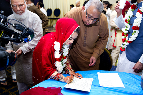 Reham Khan signing the wedding contract as her father looks on