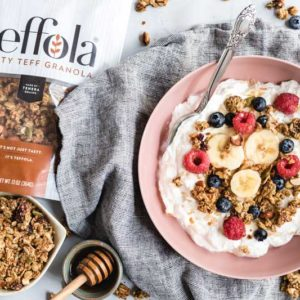 teffola granola next to yogurt bowl with berries